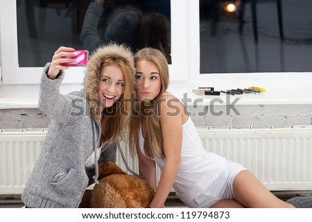 Two girls are taking picture with mobile phone to publish it in social network - stock photo
