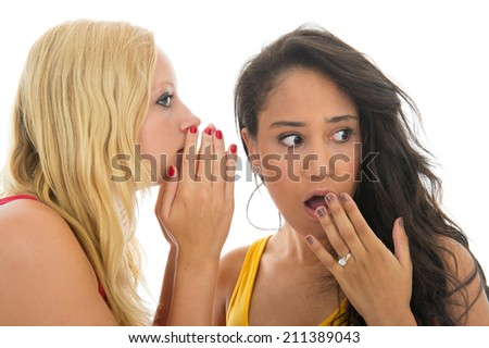 Two girls are talking secrets to each other isolated over white background - stock photo