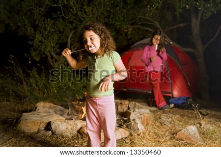 two girls at a camp eating marshmallow - stock photo