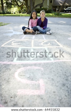 Two girls at home on driveway sitting in front of hopscotch board (7 years) - stock photo