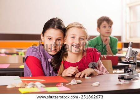 Two girls, best friends in school on science class - stock photo