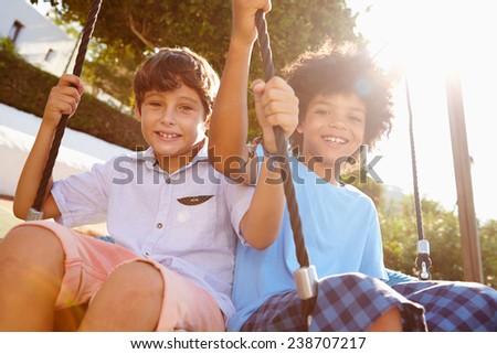Two Girls Boys Fun On Swing In Playground - stock photo