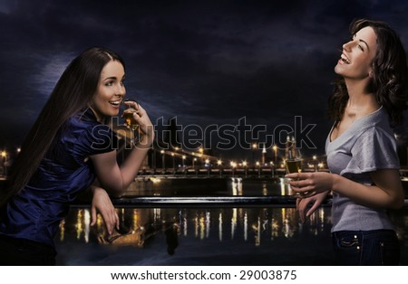 Two girls celebrate a moment with some wine - stock photo