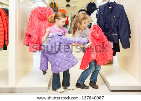 Two girls choose clothes in a store childrens clothes - stock photo