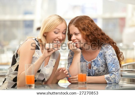 Two girls discuss men in a cafe - stock photo