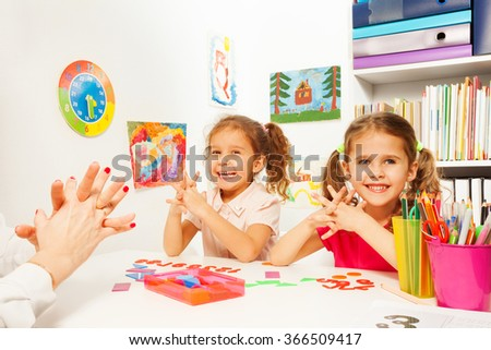 Two girls doing finger exercises as her teacher - stock photo