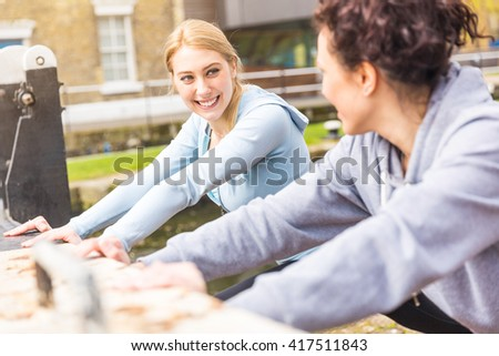 Two girls doing stretching exercises outdoors in London. They are caucasian women, looking each other while working out. Spring season and urban setting. Healthy lifestyle and fitness concepts. - stock photo