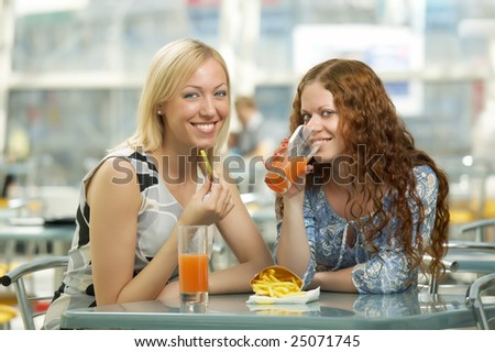 Two girls eat in fast food cafe - stock photo