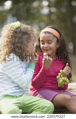 Two girls eating grapes - stock photo