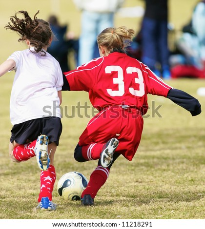 Two girls fighting for the soccer ball during a game - stock photo