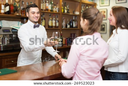 Two girls flirting with smiling young handsome barman at bar  - stock photo