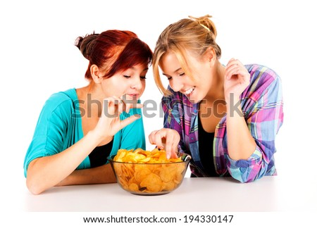 two girls, friends with chips, white background - stock photo