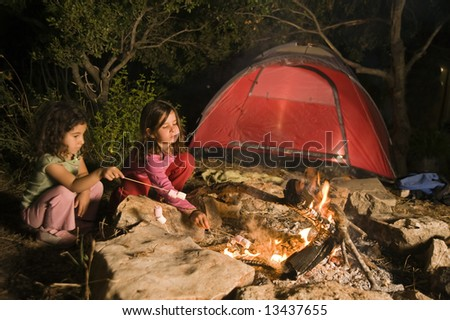 two girls having fun at a bonfire eating marshmallow - stock photo