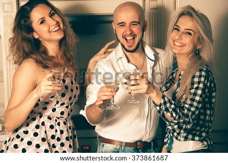 two girls having fun with a guy at a party with a glass of martini. Celebrate, disco, party, nightlife, entertainment, friendship concept. - stock photo