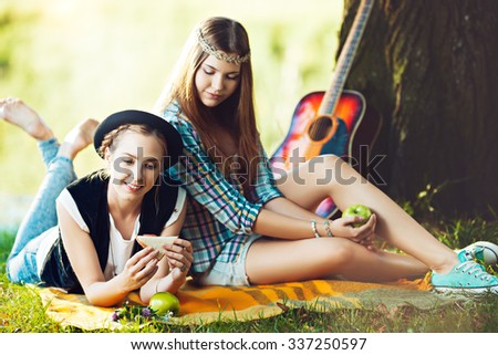 Two girls having picnic in the park - stock photo