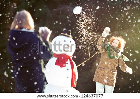 Two girls having snowball fight. One of them throwing snowball is in focus, motion blur - stock photo