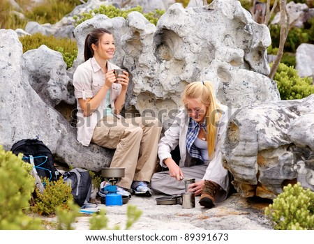 two girls hiking in the great outdoors have stopped to have some coffee and cook some canned food - stock photo