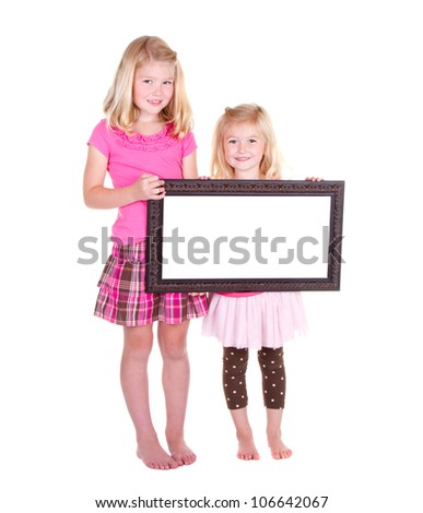 Two girls holding a blank frame room for copy space - stock photo