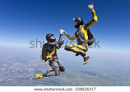 Two girls holding hands parachutist. - stock photo