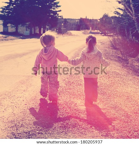 Two girls holding hands walking on road - instagram effect - stock photo