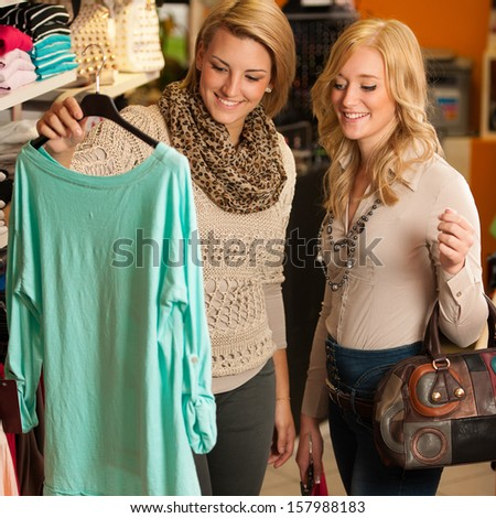 Two girls in a clothes shop - women on shopping - stock photo