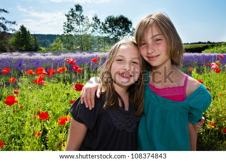 Two girls in a field of colorful, purple summer lavender flowers. - stock photo
