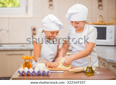 Two girls in costumes chefs prepare meals in the kitchen - stock photo