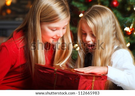 two girls in front of christmas tree and fire place opening a gift - stock photo