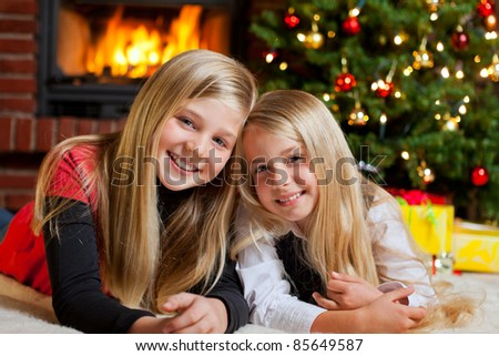 two girls in front of christmas tree with gifts and fire place - stock photo