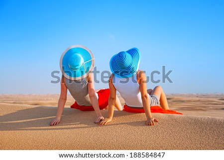Two girls in hats relaxing in the desert  - stock photo