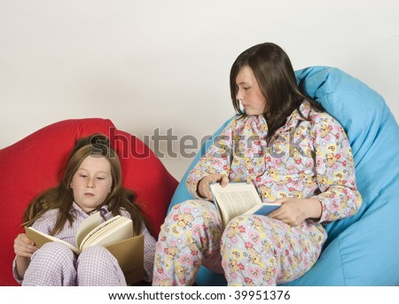 two girls in pajamas(sisters - 7 years and 13 years) sitting on beanbag chair and reading  MR - stock photo