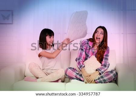 Two girls in pajamas sitting on sofa - stock photo