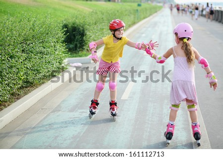 Two girls in roller skates, knee and elbow pads ride on rollers and give each other a high five - stock photo