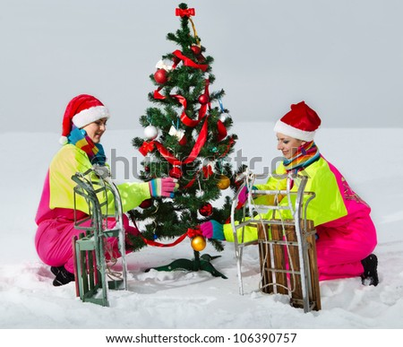 Two girls in Santa Claus cap decking up the Christmas tree at snow - stock photo