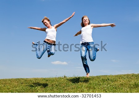 Two girls jump on a green grass against the blue sky - stock photo