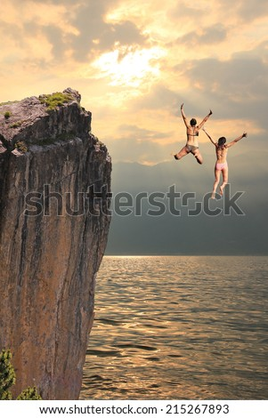 two girls jumping from cliff rock, coastal landscape in the evening - stock photo