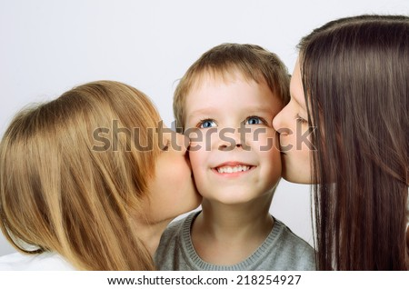 two girls kissing little cheerful boy. horizontal format - stock photo