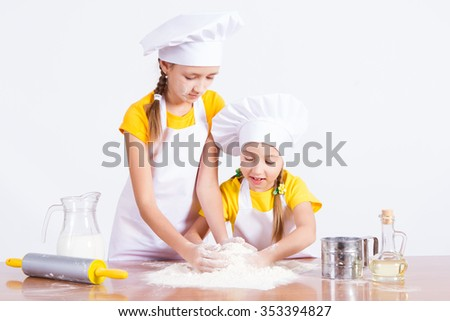 Two girls knead the dough, on a white background - stock photo