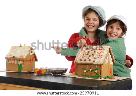 Two girls laughing and pointing at the gingerbread houses they've just decorated.  Isolated on white. - stock photo