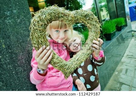 Two girls look through decorated heart into the camera - stock photo