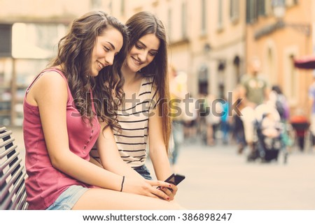 Two girls looking at a smartphone and sitting on a bench. They are two teen girls on a sunny summer day. Friendship, technologies and lifestyle concepts. - stock photo