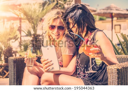 Two girls looking at phone outdoor drinking cocktails - stock photo