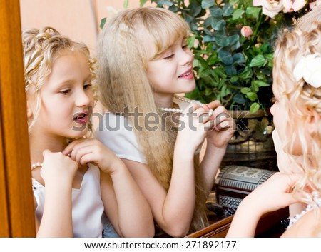 Two girls looking at themselves in mirror and trying on beads - stock photo