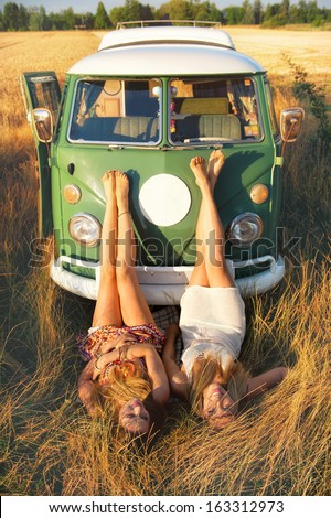 two girls lying in the grass in front of an old minibus - stock photo
