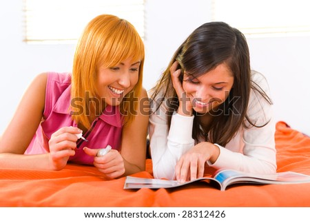 Two girls lying on bed and browsing magazine. One of them painting her nails. Front view. - stock photo