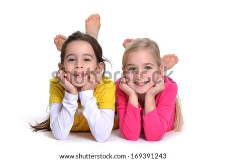 two girls lying on stomach white background - stock photo