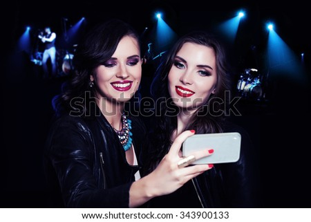 Two Girls Making Selfie on Music Party Background. Women Relaxing and Making Selfie  - stock photo