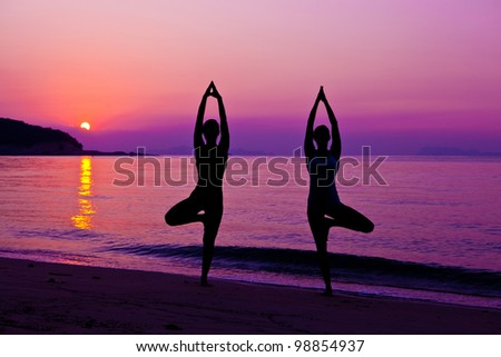 Two girls making yoga on the beach in sunset - stock photo