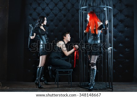 Two girls mistress dominate man. They tied him up and beat whip as punishment. - stock photo