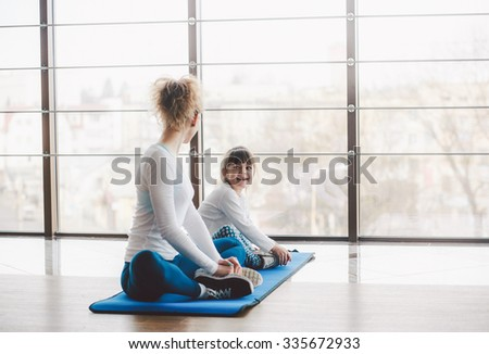 Two girls of different ages makeing yoga - stock photo